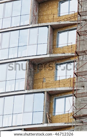 Building under construction with heat insulation and windowed balconies