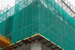 Building under construction wrapped green protection safety net.