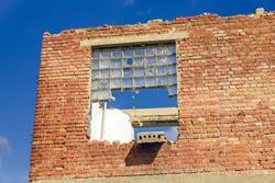 Building walls. Collapsing building. Old brick. Broken windows.