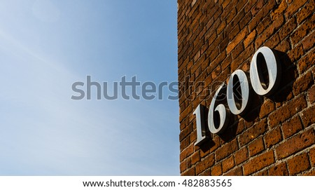 Building with address sign saying 1600 against blue sky on a sunny day