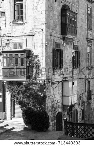 Building with traditional colorful maltese balcony in historical part of Valletta. Red windows decorated with begonville on the facade of a house in Malta. Black and white picture #713440303