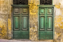 Building with traditional maltese doors in historical part of Valletta. Entrance to an abandoned house on the island of Malta