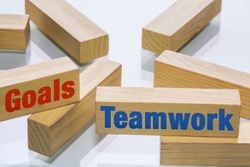 Building wooden blocks arranged to show colaboration between different company departments to achieve goals and encourage teamwork.