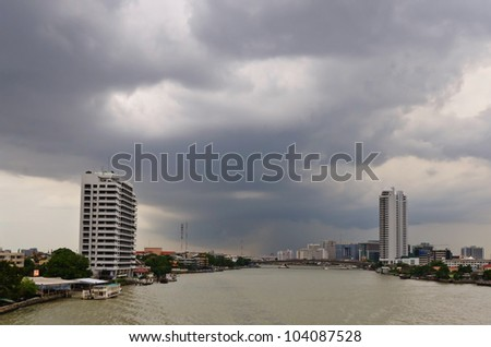Buildings along the Chao Phraya River and nimbus on the sky