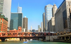 Buildings and bridges, with an elevated train, looming above the Chicago River
