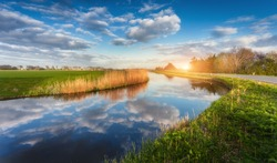 Buildings and trees near the water canal at sunrise in Netherlands. Colorful blue sky with clouds. Spring landscape in Holland. Rural scene. Cloudy sky reflected in water. Nature background. Sunshine