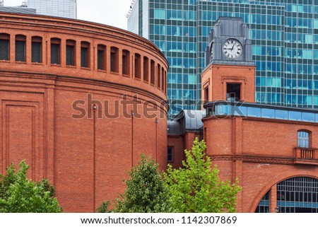 Buildings of Stary Browar with a clock tower and facade of a modern office building  in Poznan Zdjęcia stock ©