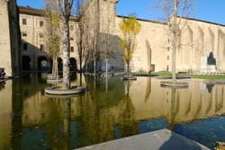 Buildings of the Pilotta in Parma. Fountain with pond and poplar trees. Emilia Romagna, Italy.