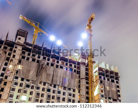 buildings under construction with cranes and illumination at dark night