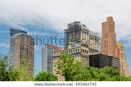Buildings with blue sky and clouds with summer trees at base. #692466745