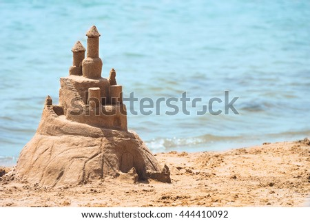 Built House sand castle with towers on the south shore of the sandy beach blue sea