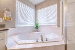 Built in bathtub at the corner of a well lighted home bathroom with two windows