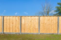 Built new horizontal wooden fence construction in dutch backyard