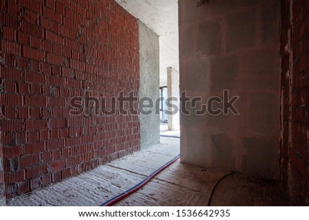 Built structure construction site of residential apartment building with sun bright light in dark narrow red brick wall corridor. Interior in progress to new house  #1536642935