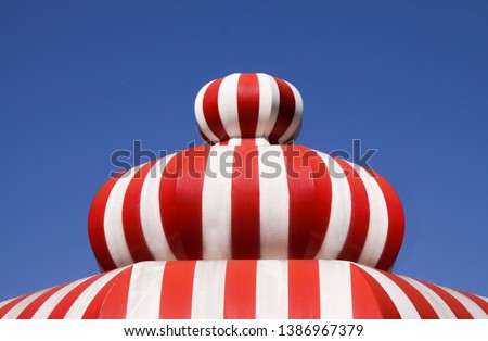 Built structure like fluffy candy or balloon with red and white stripes - close up with blue sky background #1386967379