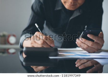Buisness accounting. Man accountant using calculator to calculate business data, financial report, using mobile smart phone and taking note on notepad in modern office, close up, dark tone