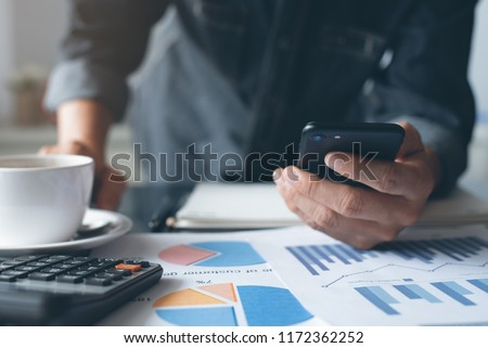 Buisness accounting. Man accountant using mobile phone. Businessman working, reviewing business marketing financial report with cup of coffee, calculator on desk in modern office, toned, close up