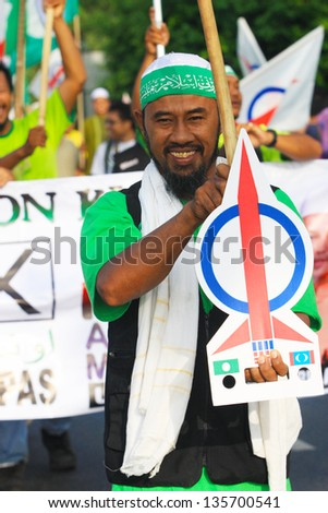 BUKIT KATIL, MALACCA, M'SIA-APR 20: Pakatan Rakyat supporter holds a sign to give support to candidate Apr 20, 2013 in Bukit Katil, Malacca, Malaysia. An election will be held on May 5, 2013