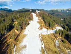 Bukovel Aerial View of the Ski Resort in Mountains With Artifical Snow at Low Season in Bukovel. Warm weather Without Snow. Ski Track in Early Winter