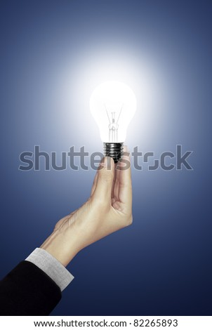 Bulb light in woman hand on blue background