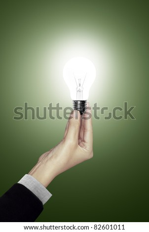 Bulb light in woman hand on green background