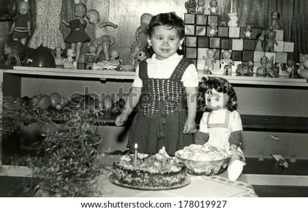 BULGARIA - APRIL 1, 1983:  girl on her birthday, the village Vodice, community Popovo, Targovishte region, Bulgaria, April 1, 1983. Name od girl is Tanya, 2 years old