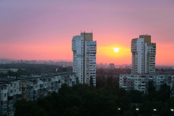 Bulgaria summer sunset in the capital Sofia with big stone massive panel blocks and green trees underneath colorful vibrant colors in the sky lots of radiant yellow and purple and pink copy space comp