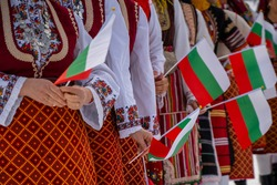 Bulgarian Flag. Woman holding Flag of Bulgaria in traditional clothing. Day of Liberation parade. National holiday with people celebrating. Patriotic scene people waving flags.