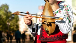 Bulgarian folk musician - violinist in traditional national costume plays an old stringed instrument - gadulka Blurred city street in background. Plovdiv Bulgaria. Bulgarian folklore and culture