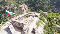 Bulgarian Medieval fortification structure to visit on a hill. Balkan stronghold and antique scenery. Holy place for tourist on a valley. Bulgaria flag on rock fort. Eastern europe place. Asenovgrad