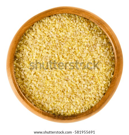 Bulgur in wooden bowl. Uncooked cereal food, most often made from groats of durum wheat. Also called burghul, a kind of dried cracked wheat. Isolated macro food photo close up from above over white. Stockfoto ©