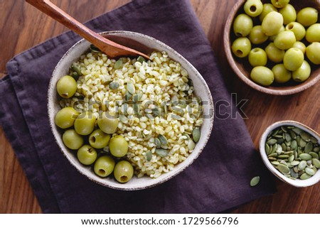 Bulgur with green olives and pepitas, healthy nutrition easy recipe from long-stored food. Foto d'archivio ©