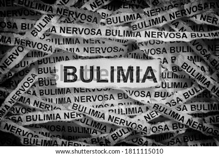 Bulimia. Torn pieces of paper with the word Bulimia. Concept Image. Black and white. Close up. Сток-фото ©