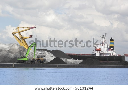 Bulk cargo being loaded onto bulk carrier in port