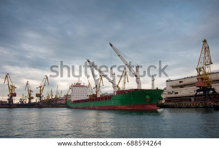 Bulk cargo ship under port crane bridge, Odessa, Ukraine. Odessa Marine Trade Port. Large container vessel. Industrial container freight. Shipping port. Industrial background. #688594264
