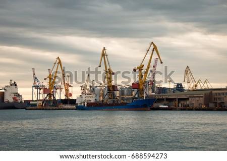 Bulk cargo ship under port crane bridge, Odessa, Ukraine. Odessa Marine Trade Port. Large container vessel. Industrial container freight. Shipping port. Industrial background. #688594273