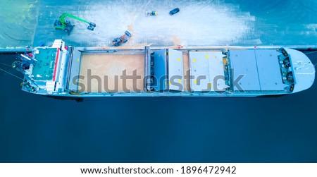 Bulk carrier ship at port loading grain into open holds. stock photo