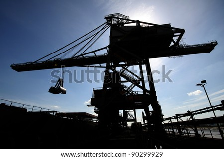 Bulk carrying vessel and un-loader crane. - stock photo