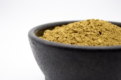Bulk Kratom powder in a black bowl isolated on a white background.