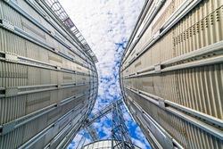 Bulk plant storage low angle blue sky. Agricultular metallic corn tower. Steel tank of wheat. Metallic tank.