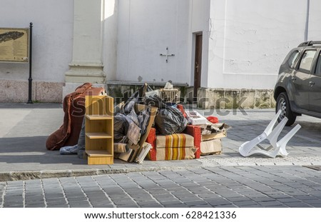 Bulky waste on the street. Broken beds, chairs, garbage furniture on pavement ready for bulky waste collection. Symbol of moving, garbage, throw-away society. Photo stock ©