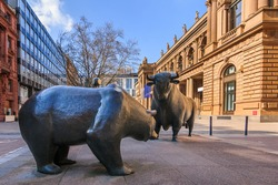 Bull and bear as a symbol figure. Place in front of the building of the Frankfurt Stock Exchange. Commercial buildings with a brown facade in the sunshine and blue sky with clouds
