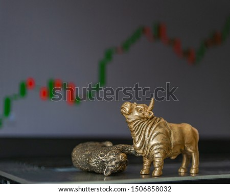 Bull and bear as symbols of stock trading on a blurred background of price graphics. The concept of symbolism of commodity and financial world markets. #1506858032