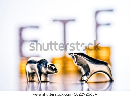 Bull and bear with stacks of coins and the letters ETF in the background