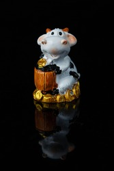 Bull as a symbol of Chinese New Year. A small plastic toy cow figurine with barrel or chest full of money. Reflection on black background. 2021 year is a year of white metal ox in China