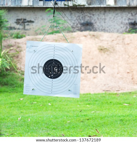Bull eye target hanging in shooting range with bullet hole inside