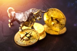 Bull figurine standing on bitcoins, concept of bullish view to future of cryptocurrencies