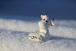 Bull Little Statuette Symbol of 2021 Year in Lunar Calendar. Horned White Cow Holding Box Full of Wealth and Health on White Fluffy Snow