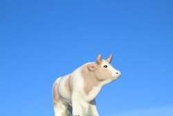 Bull Little Statuette Symbol of 2021 Year in Lunar Calendar. Horned White Spotted Cow Figurine against Clear Blue Sky