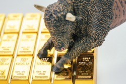 Bull market in gold investment concept, closed up of bull figure on gold bar or ingot.